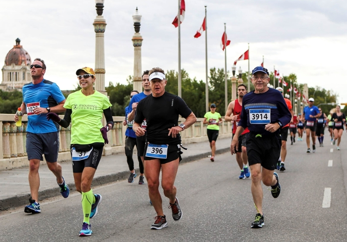 Dean Preston Smith (right) runs in the Queen City Marathon in Regina.
