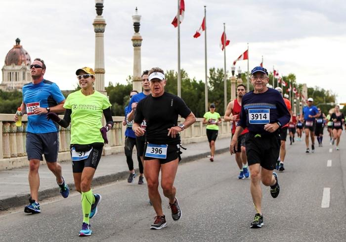 Dean Preston Smith (right) runs in the Queen City Marathon in Regina.